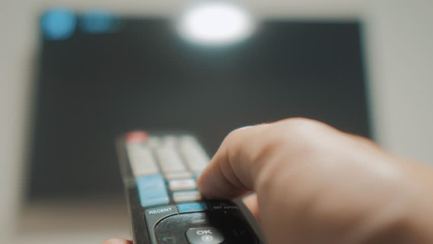Man hand holding the TV remote control and turn off smart tv. Channel surfing. Close up mans hand lifestyle holding TV remote control and changing TV channels. blurred background | Shutterstock HD Video #1021321348