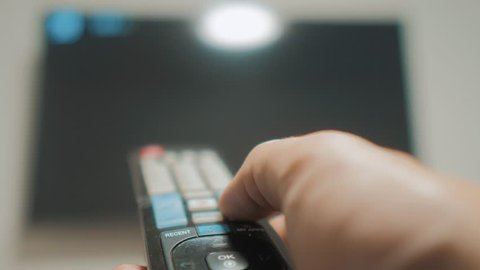 man hand holding the TV remote control and turn off smart tv. Channel surfing. Close up mans hand lifestyle holding TV remote control and changing TV channels. blurred background