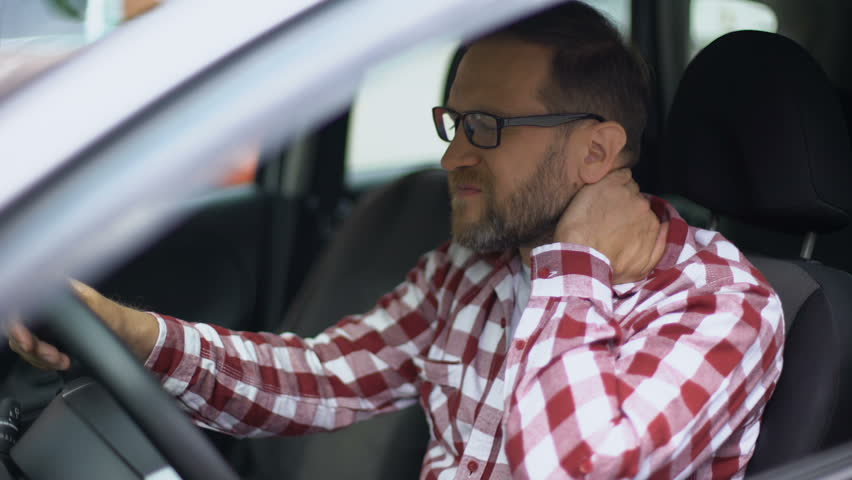 Tired man sitting in car suffering neck discomfort, spinal problem, cervicalgia   Shutterstock HD Video #1021327288