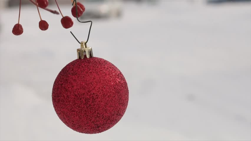 Red ball decor hanging on a branch in a blurry two cars moving slowly behind it | Shutterstock HD Video #1021368118