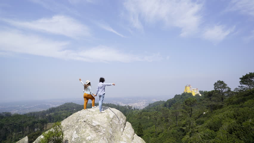 Back view of young man and woman raising hands and admiring picturesque view while standing on rock in wonderful park in Sintra, Portugal