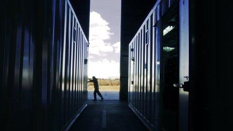 Warehouse Worker Pushing Metal Door.   Cloudy Background.