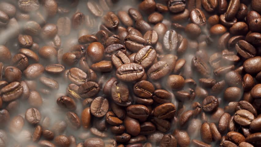 Fragrant coffee beans are roasted in a frying pan, smoke comes from coffee beans. The whole composition scrolls slowly around the camera.  | Shutterstock HD Video #1021452328