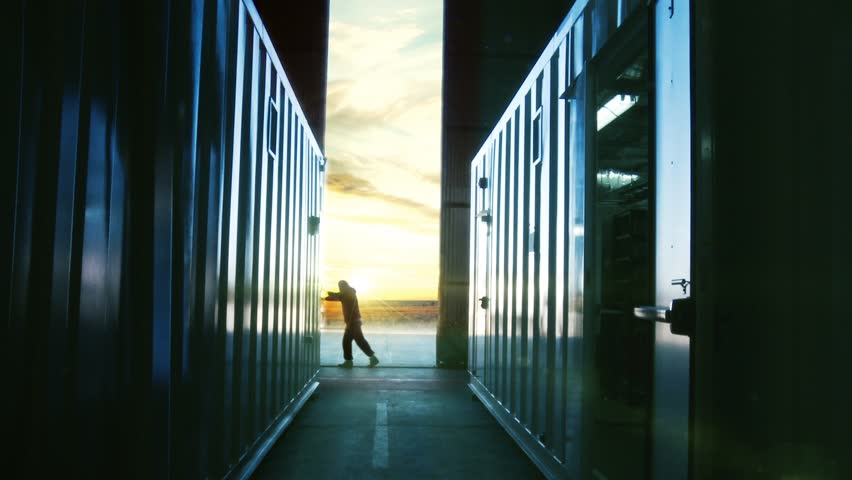 Man Opening Door of a Container Warehouse at Dusk. Orange Sky in the Background.