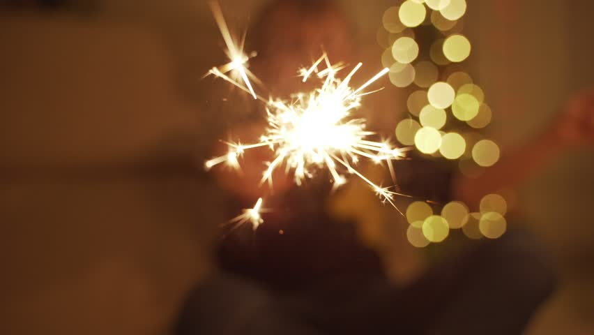 The boy holds a Sparkler and laughs. Sparklers. the sparklers in his hands. New year mood. Christmas tree. Lights. Handsome boy. Children #1021463848