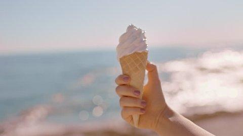 close up hand woman holding ice cream vanilla flavored dessert on beautiful sunny beach enjoying summer vacation eating soft serve