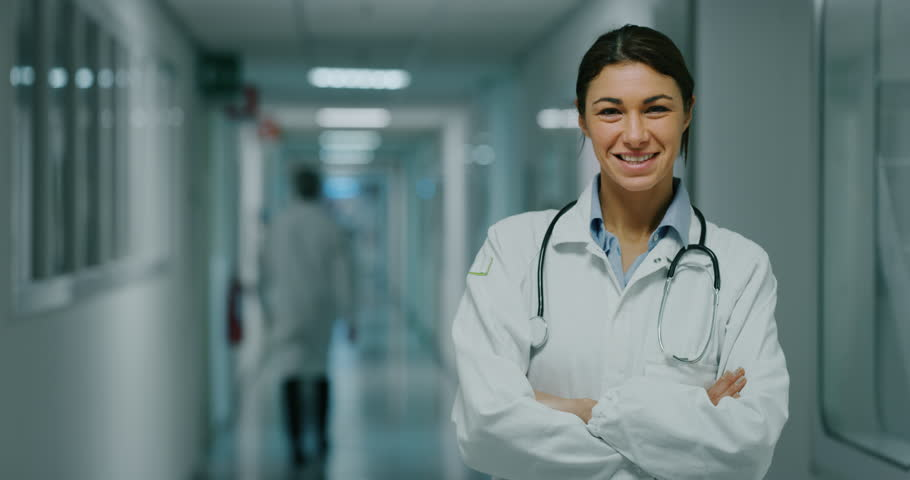 Portrait of smiling female doctor satisfied with his job in a corridor of a hospital. Concept of medicine, technology, health care and people, hospital