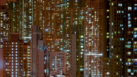 Day to night transition timelapse of Hong Kong apartment buildings. Chinese crowded city with lights turning on and off at midnight. Fast paced modern Asian night-scape time lapse in urban metropolis