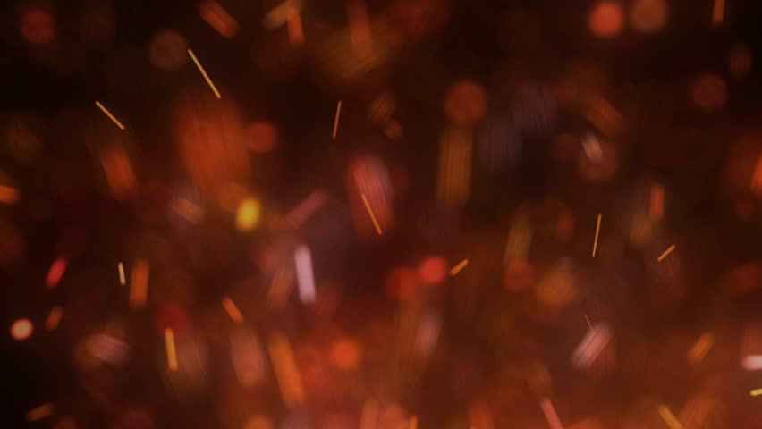 Orange, red, and yellow particles resembling fire or embers float upward past the camera | Shutterstock HD Video #1021546018