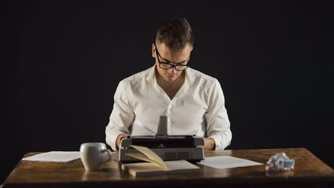 Concentrated writer collecting all pages of the chapter, writing another amazing masterpiece on vintage typewriter at wooden desk in black background