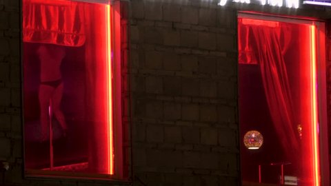 Surveillance room privat with red neon. Women dance strip for men. Girl undress near the window. Dance of women without clothes on street of Amsterdam red light district. Light erotica in nightclub 4k