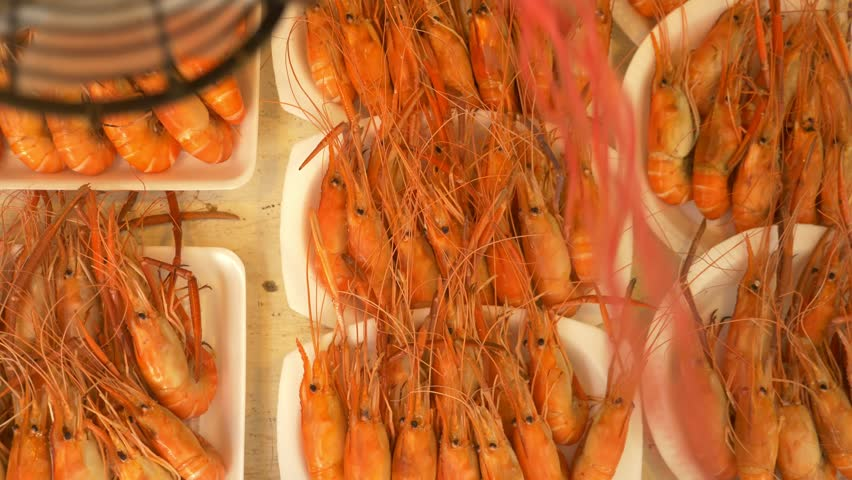 grilled prawns on the counter of the street market, a device for flies away.