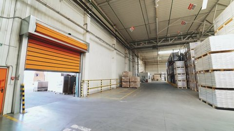 VINNITSA, UKRAINE - MAY 2018: Orange rolling door of the warehouse is closing. Rolettes work with the help of automation. Motion of rolling door to down