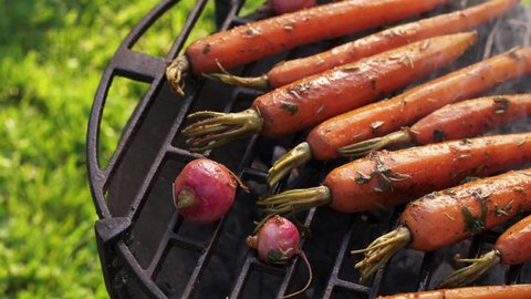 Grilled carrots in a herbal marinade on a grill plate, outdoor, top view, 4k. Grilled vegetable, vegetarian food, bbq