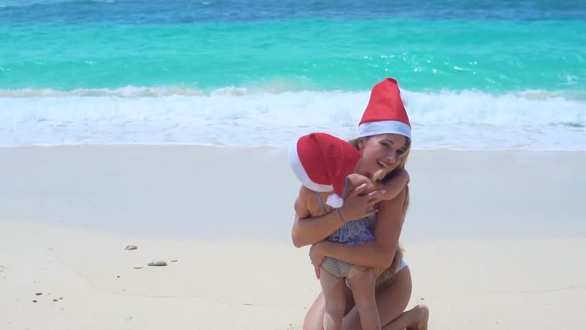 Beautiful mother and her pretty daughter in swimsuits and santa hat stand on the beach ,looking at the sea. Merry Christmas. | Shutterstock HD Video #1021690318