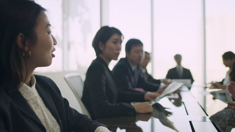 Group of Japanese business people working together around a large table in a conference room with soft natural lighting. Medium shot on 4k RED camera.