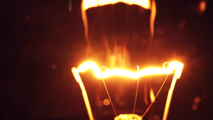 Filament of Light bulb turning on and off on black background. 4K video with shallow depth of field focus. | Shutterstock HD Video #1021784158