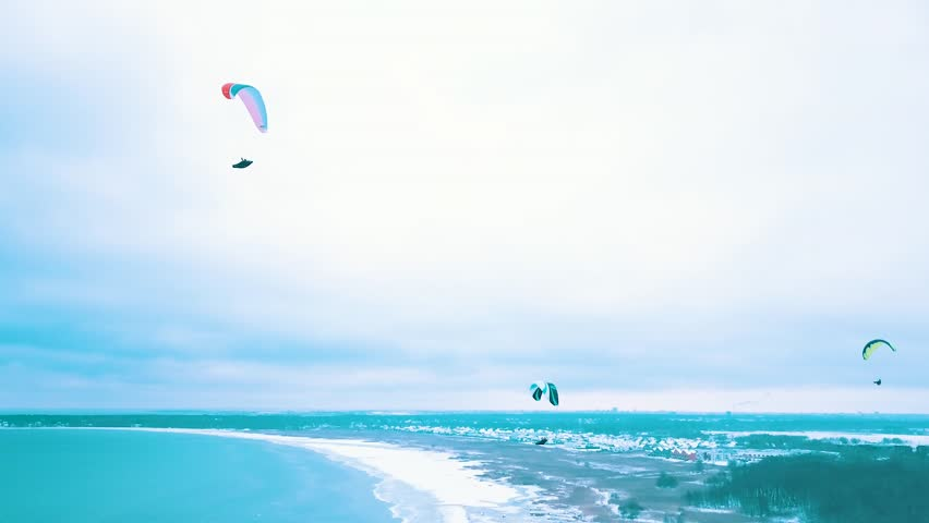 People flying on parachutes at the winter by the cliff above the sea | Shutterstock HD Video #1021792558