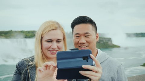 Active married couple taking a selfie on the phone at Niagara Falls, close-up