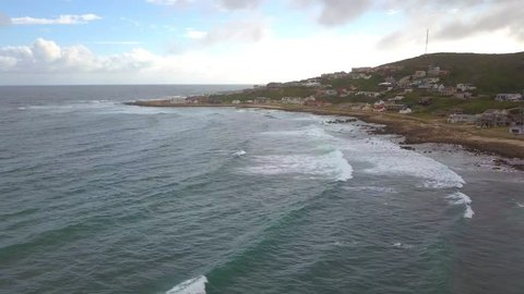 Aerial of drone flight along the coast and houses at Jongensfontein on Garden Route in South Africa