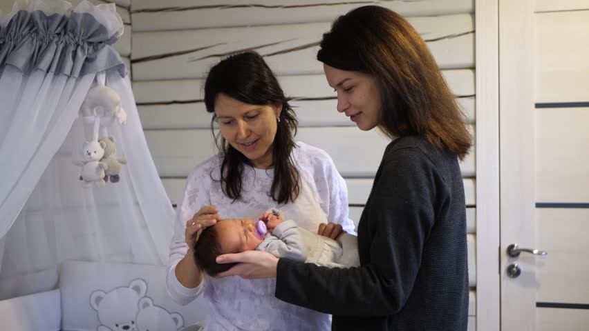 Beautiful young mother giving to hold her new born baby to her grandma for a first time