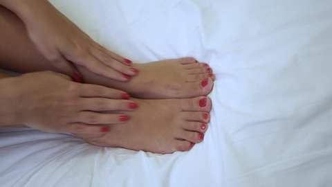 Close up top view of female feet and hands with beautiful fresh professional gel polish pedicure and manicure. Woman pampering her tired legs after difficult day while laying in bed. 4k video footage.