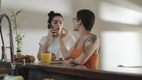 Two lesbians at home, girl eating fruit and food for snack, partner talking on mobile telephone. Happy homosexual people domestic lifestyle. Young women, gay girls, same sex partners kiss for love