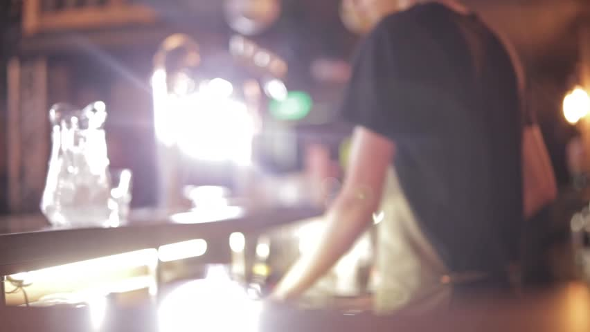 Young Guy Bartender Makes An Alcoholic Drink Standing Behind The Bar With Bright Lamps. Concept Work In A Bar At Night | Shutterstock HD Video #1021989808