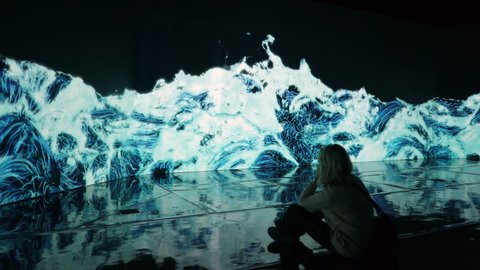 "HELSINKI, FINLAND - JAN 06, 2019: ""Massless"" Exhibition - immersive interactive graphic digital installations by a group of Japanese artists TeamLab at the Amos Rex Museum. Visitors at museum enjoy"