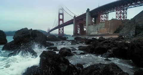 Aerial: Flying over rocky coastline & The Golden Gate Bridge in the fog. San Francisco, USA