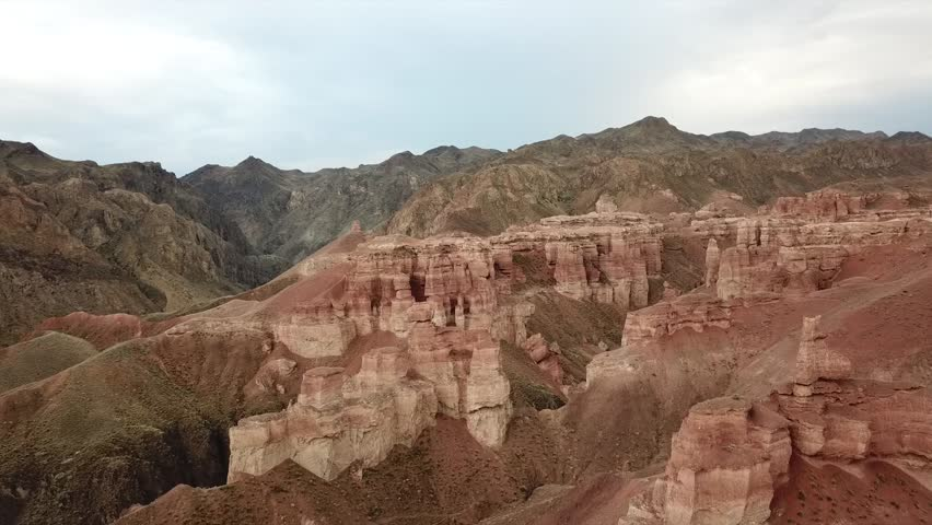 Red clay canyon. Shooting with the drone. Flying over sand castles, rocks, crevices. Ancient Charyn canyon. Visible trail, sometimes growing green grass. Gray sky over the canyon. Nature Of Kazakhstan | Shutterstock HD Video #1022069008