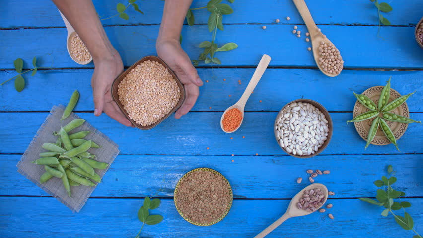 Legumes on wooden ecological background. Beans are located in unusual form on blue wooden table. Hands take bowl with peas from table. Bean cultures in wooden bowls. peas lie on napkin.  | Shutterstock HD Video #1022099908