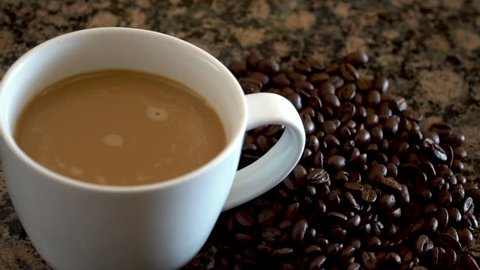 Swirling coffee with creamer in mug for breakfast. Slow motion, shot at 120 fps.