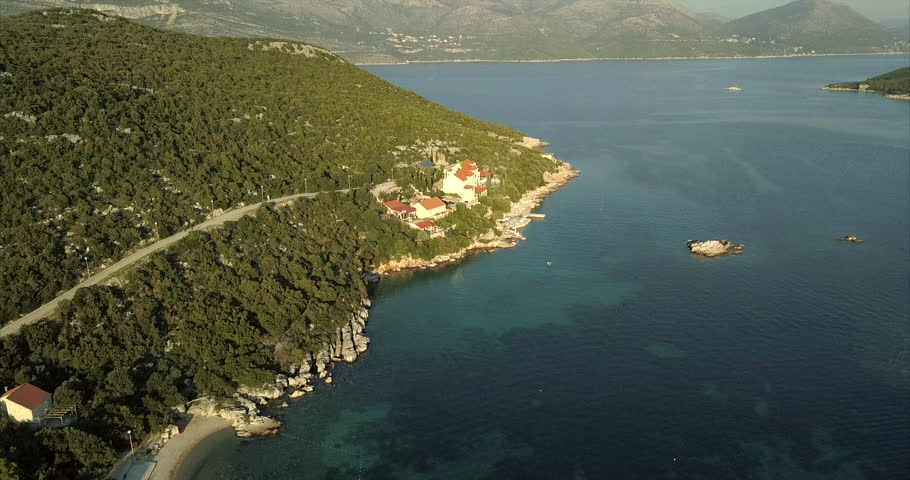 Aerial video tracking along the coast line of a small island with mainland, mountainous hills, in the distance