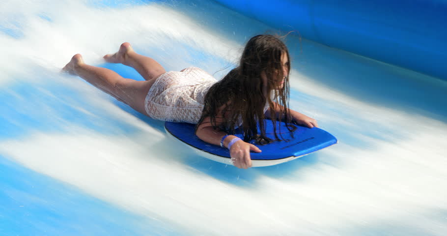LABADEE, HAITI - SEPTEMBER 25, 2018: Young girl exercising on a surf board and falling during powerful water jet stream in Labadee, Haiti, 4K