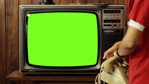"""Teenage Boy Talking On Phone, and Turns On Old Tv Green Screen. You can replace green screen with the footage or picture you want. You can do it with """"Keying"""" effect (check out tutorials on YouTube)."""
