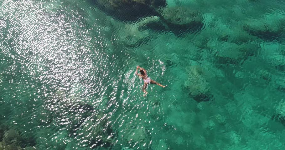 Summer image of beautiful girl swimming and lying on the back in the turquese sea water. Slim tanned body. Amazing sea landscape. Happy vacation and relaxing. Cyprus Green bay.   Shutterstock HD Video #1022112088