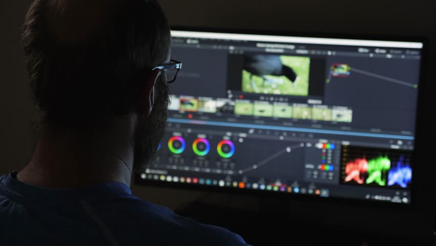 Man with beard working late at night editing and colour grading a film
