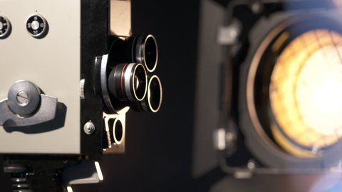 Vintage 8mm film movie camera rotating on black background. Old film camera with triple lens turret and clockwork mechanical motor. Made in USSR 1967-1975. Close-up dolly shot.