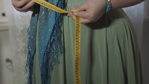 fat woman is desperate because it does not lose weight, measurement waistline