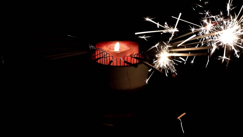 Sparklers and wax candle flames as an element of holiday decor   Shutterstock HD Video #1022181688