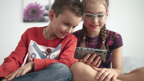 Portrait of kids looking at mobile phone at home. Sister and brother playing video games on mobile phone. Children looking gadget