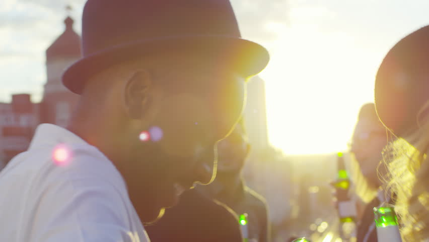 Close-up shot of young african american man in fedora hat drinking beer from bottle and dancing with group of friends at party on urban rooftop at sunset