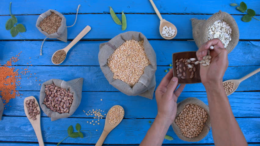 Legumes on wooden ecological background. Beans are located in unusual form on blue wooden table. Hands take colored and white beans from bags to plate. | Shutterstock HD Video #1022203228