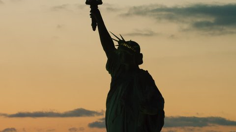 Aerial view of orbiting the Statue of Liberty on the East River, New York City, dark sunset light in winter. Shot on 4k RED camera on helicopter.