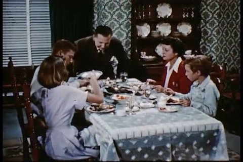 CIRCA 1950s - A family sits down and eats at a dinner table in a dining room in a home.