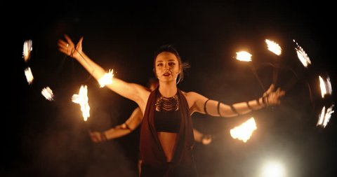 Cool female fire show artist is having a performance, flailing her equipment in darkness - slow motion 4k