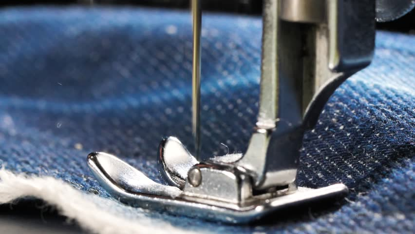 Sewing denim jeans with sewing machine. Repair jeans by sewing machine. Alteration jeans, hemming a pair of jeans, handmade garment industrial concept | Shutterstock HD Video #1022230108