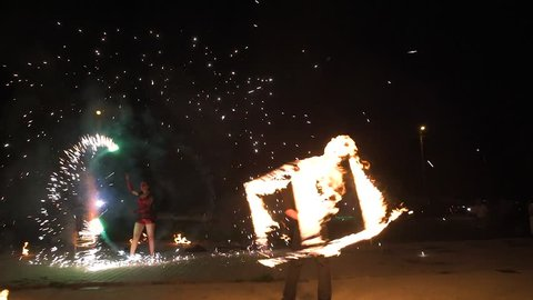 An amazing fire show at night. A man spinning fire. Long shot