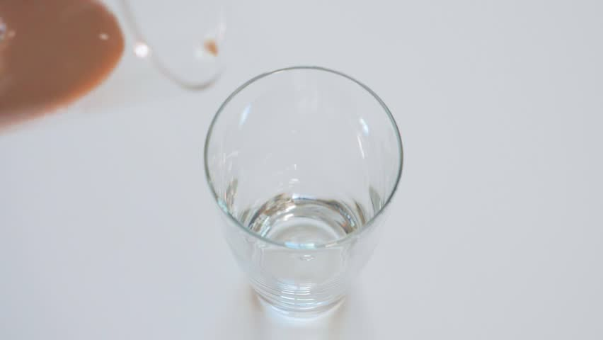 Pouring chocolate milk in drinking glass on white background, Close up slow motion | Shutterstock HD Video #1022268028